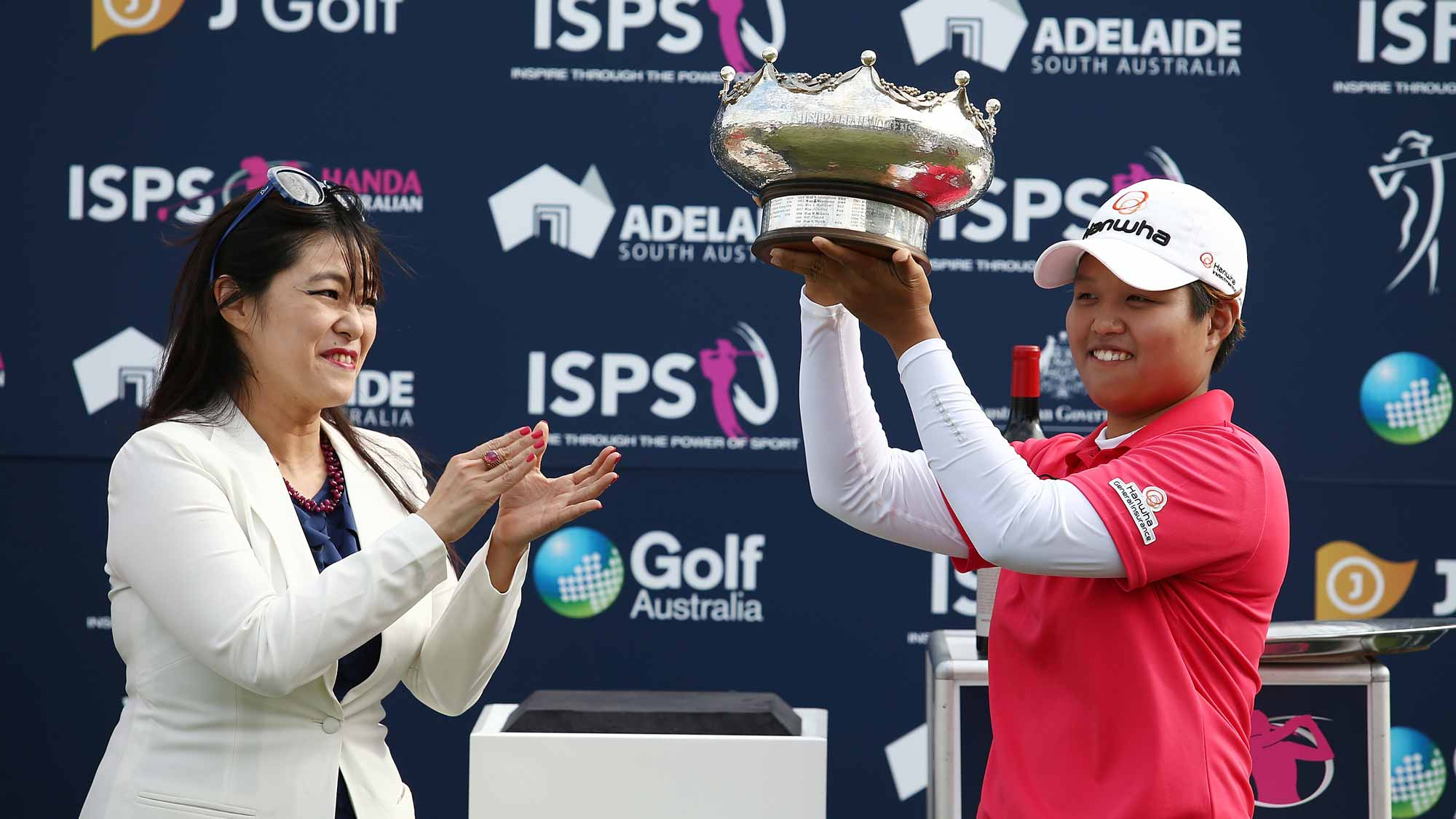 aru Nomura of Japan is presented with the winners trophy by Midori Miyazaki after winning the Women's Australian Open